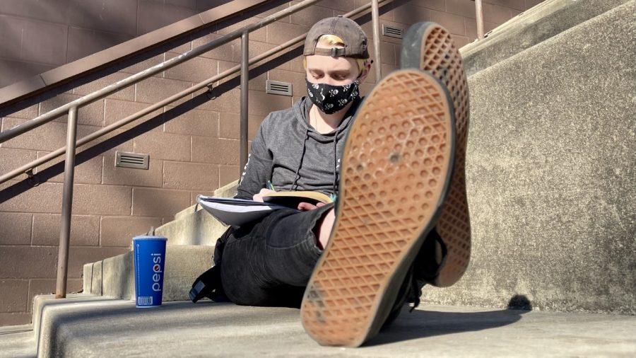 Kaden Howard, freshman English major, takes advantage of the warm weather Wednesday by reading and studying on the Mellin Steps at the Doudna Fine Arts Center.