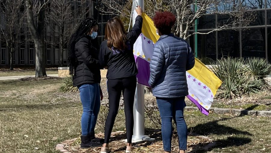 Eastern students Nyjah Lane (left), a graduate student studying College Student Affairs, Starr Winburn, a graduate student studying counseling, and Justice McGruder, a graduate student studying counseling, prepare to raise the Suffragist Flag Monday afternoon.