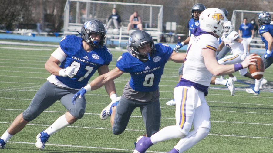 Eastern freshman safety Jordan Vincent (0) and sophomore defensive lineman Tim Varga (97) chase Tennessee Tech quarterback Bailey Fisher out of the pocket in a game March 21 at O'Brien Field. Vincent had 2 tackles and Varga had 8 in the game, which Eastern won 28-20.