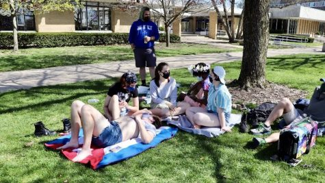 A group of students relax on the South Quad and listen to music while enjoying the weather on Friday. Many students have been spending more time outside as the weather continues to warm up.