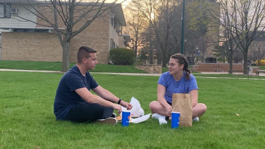 Charles Koprowski (left), a sophomore music education major, and Madeline McQueen (right), a freshman music education major, end the day with food from Stevenson Tower Dining at the Library Quad on Monday evening.