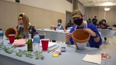 Claudia Donovan (left), a sophomore emergency management and disaster preparedness major, and Luke Reeves, a sophomore engineering technology major, paint pots at Thursday