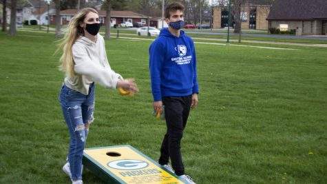 Katie Alexander (left), a junior political science major, and Francesco Romano (right), a junior computer science major, play a game of bags Thursday evening. Student Government