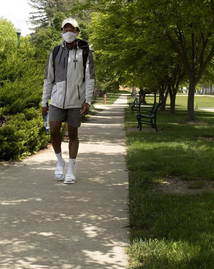Tadz Mhonde, a recent graduate, walks across campus on Thursday afternoon. Mhonde said he was taking a moment to walk around campus before he begins his work as a graduate student in the fall. He said he was excited to graduate and that it felt