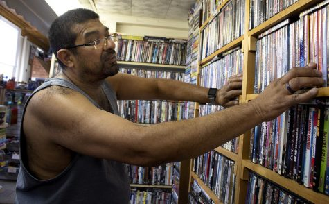 """Daniel Cordeor looks for the movie """"Mad Max"""" in The Corner Spot at the square Monday afternoon. Cordeor is an avid movie watcher and collector; he said he has over 400 DVDs and around 30 Blue-Rays. His collection is mainly movie series and movies from his childhood and he"""