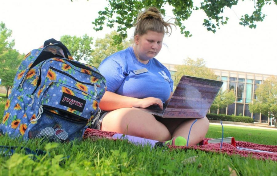 Valen Fulton, a conference assistant for housing and dining and an art major, sits outside at the Library Quad to get some homework done before she goes to work. She said that she had been inside for most of the day and decided to come outside to enjoy the nice weather while she could.
