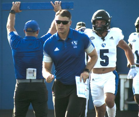 Eastern head coach Adam Cushing leads wide receiver Matt Judd (5) and the rest of the team onto the field prior to the game against Indiana State Aug. 28 in Lantz Arena. The Panthers lost the game 26-21.