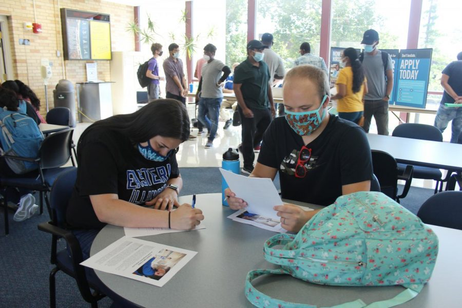 Audrey Buss, a freshman science education major, fills out a job application while her husband, Luke Mason, is there to support her.