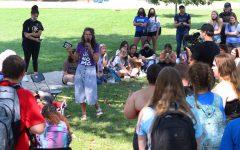Sister Cindy preaches and tells stories about her life to students listening in library quad in front of the Mellin steps.