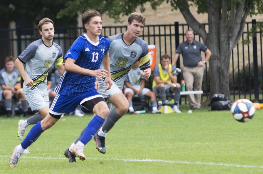 Eastern midfielder Chad Hamler (13) races two defenders to the ball in Eastern's match against Purdue Fort Wayne on Sept. 3 at Lakeside Field. Eastern lost the match 1-0.