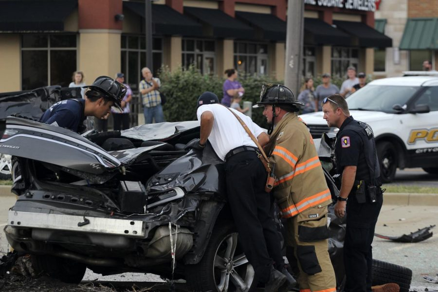 Members from the Charleston Fire Department and Police Department searach the car of the deceased man who drove onto oncoming traffic to cause the five-car accident that happened an the intersection of Lincoln Avenue and University Drive Sunday afternoon.