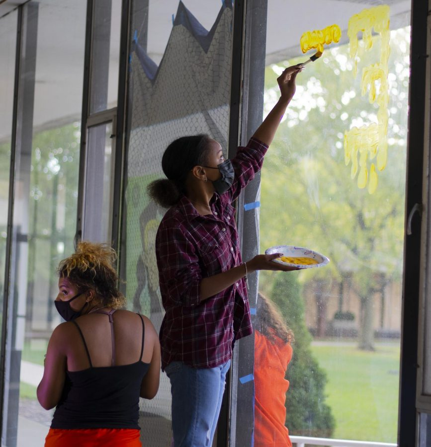 Sabrina Rodgers, a freshman computer science major, and Malaiah Mccrory, a freshman psychology major, paint a Kim Possible theme on the windows of Andrews Hall for Neighborhood Week Window Painting.