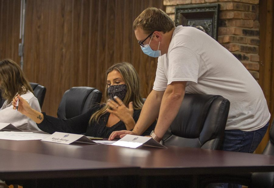 Graduate adviser Justin Richards who studies communications helps student senator Natalie Mitlyng, a senior pre-veterinary biology major with ideas on possible events for their department to run at the Oct. 5 Student Government meeting.