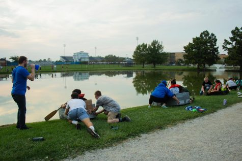For Neighborhood Week, different residence halls compete in a relay boat race at the campus pond.