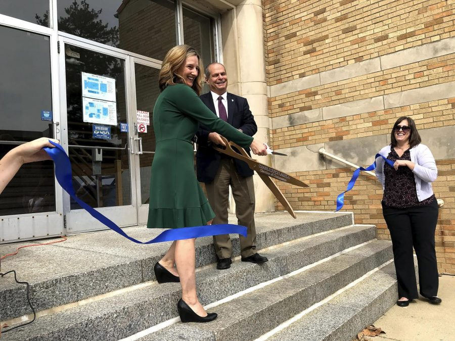 Anne Flaherty and President Glassman cut the ribbon to showcase the new campus food pantry in McAfee.