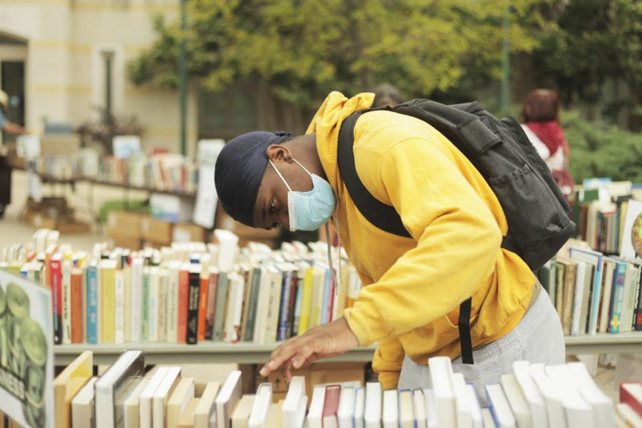 Xsaviar Hunter, a junior chemistry major, sifts through books during the book sale Wednesday afternoon.