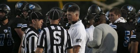 Eastern head coach Adam Cushing (center) talks with the officials during a timeout in the game against Illinois State on Sept. 18 at OBrien Field. Eastern lost the game 31-24 to the Redbirds in the 109th Mid-America Classic.