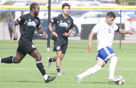 Eastern midfielder Jonas Castelhano dribbles away from a pair of opponents in a match against Omaha on Oct. 9 at Lakeside Field. Castelhano had an assist in the match, a 2-1 loss for Eastern.
