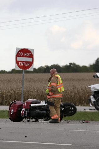 A member of the Charleston Fire Department investigates the motorcycle from the two-vehicle crash on Route 16 and Deerpass Road Monday evening.