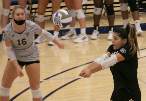 Eastern libero Christina Martinez Mundo (right) receives a serve in a match against Southern Illinois-Edwardsville on Oct. 5 in Lantz Arena. Martinez Mundo had a game-high 19 digs in the match, which Eastern lost 3-1.