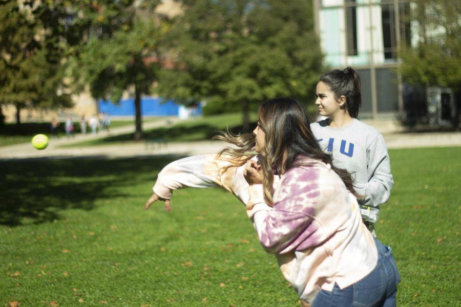 Paulina Sanchez, a junior spanish major, throws a tennis ball at the dunk tank target.