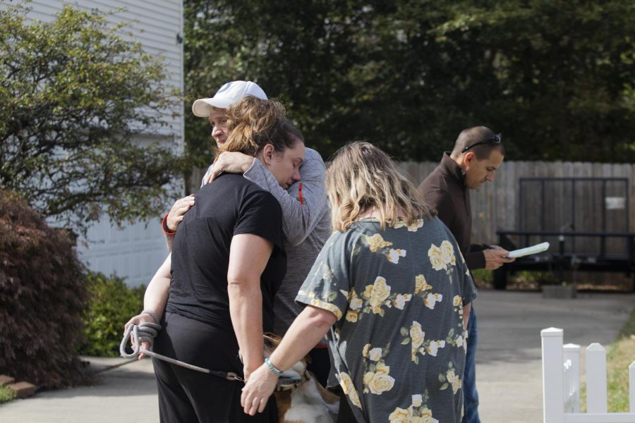 The parents of the woman whose house caught on fire, hug her while they wait outside.