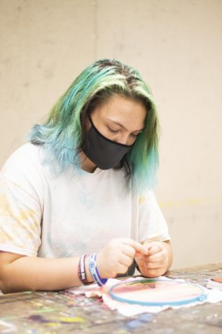 Diana Maggi, a freshman biological sciences major, creates a domestic life art project in Doudna Fine Arts Center.