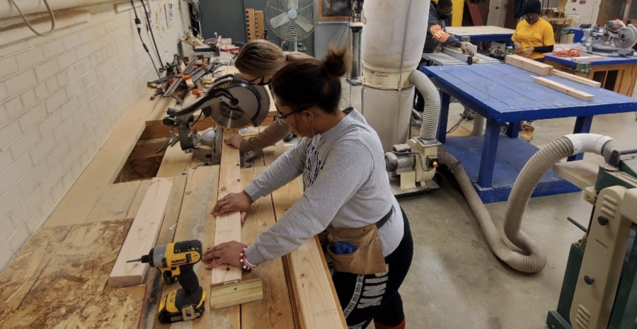 Raven Ramsey, senior construction management major and Katherine Farrell, a graduate student studying sociology, cut wood in a project for the Construction Club.