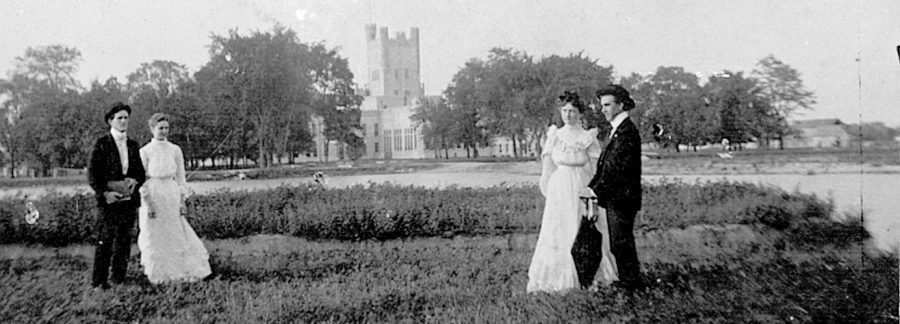Two couples posed by Lake Ahmoweenah, with Old Main in background, July 1902. Pictured from left to right are Frank Henderson, Ethel Carnes, Grace Moore, and Charles Henderson.